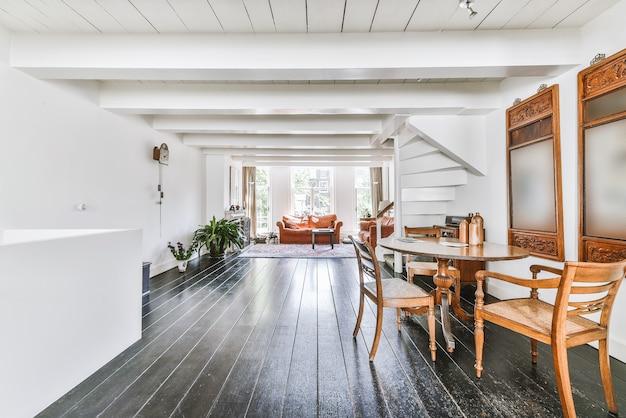 Chambre ensoleillée chambre avec canapés en terre cuite et tapis ornemental sur plancher en bois près de l'escalier menant au deuxième étage