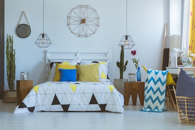 Chambre folklorique avec horloge en cuivre décorative sur mur blanc au-dessus du lit. concept de chambre folklorique