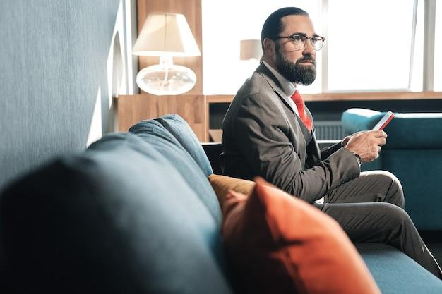 Chambre d'hôtel confortable. homme d'affaires barbu aux cheveux noirs assis dans une chambre d'hôtel confortable tout en ayant un voyage d'affaires