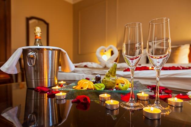 Chambre d'hôtel pour une lune de miel: une table avec une assiette de fruits et des bougies