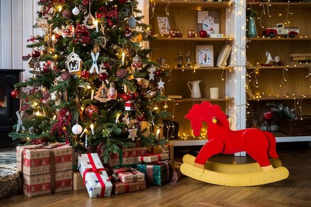 Chambre avec intérieur de noël, arbre de noël décoré de guirlande clignotante et chaise à bascule rouge