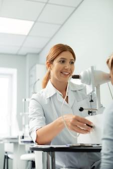 Chambre lumineuse moderne. ophtalmologiste aux cheveux roux travaillant dans une salle lumineuse moderne tout en examinant une fille