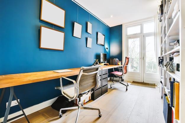 Chambre lumineuse avec murs bleus et table en bois avec ordinateur et chaises au bureau à domicile