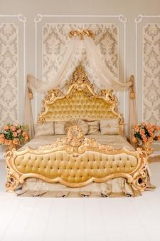 Chambre de luxe aux couleurs claires avec des détails de meubles dorés