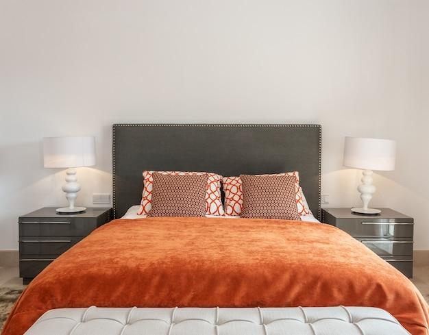 La chambre moderne comprend une chambre avec un lit et des oreillers décoratifs.