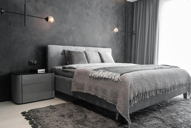 Chambre moderne avec des intérieurs gris tendance, un grand lit king-size et des lampes