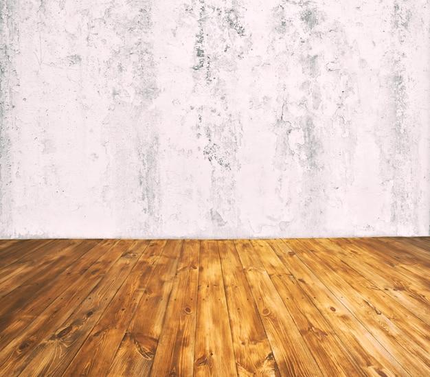 Chambre avec mur de béton gris et plancher en bois avec beaucoup de planches