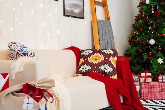 Chambre de noël joliment décorée avec sapin et canapé blanc