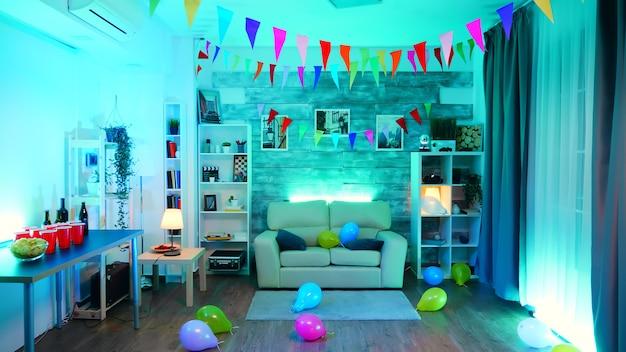 Chambre avec personne dedans décorer pour la fête avec néon, bière et frites.