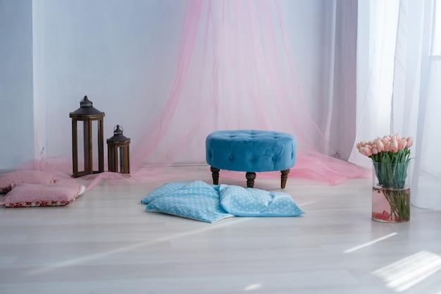 Chambre spacieuse avec lumière du soleil, siège bleu et fleurs dans un vase