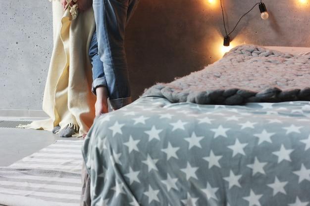 Chambre style loft, lit avec couverture grise et homme et femme en arrière-plan