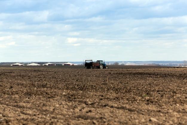 Champ agricole d'engrais - champ agricole sur lequel l'ancien tracteur pour épandre du fumier pour fertiliser la terre
