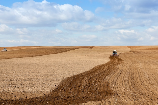 Le champ agricole, qui a labouré dans un tracteur préparant le terrain pour la plantation. printemps