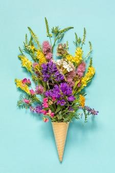 Champ de bouquet de fleurs colorées dans le cornet de crème glacée gaufre sur fond de papier bleu