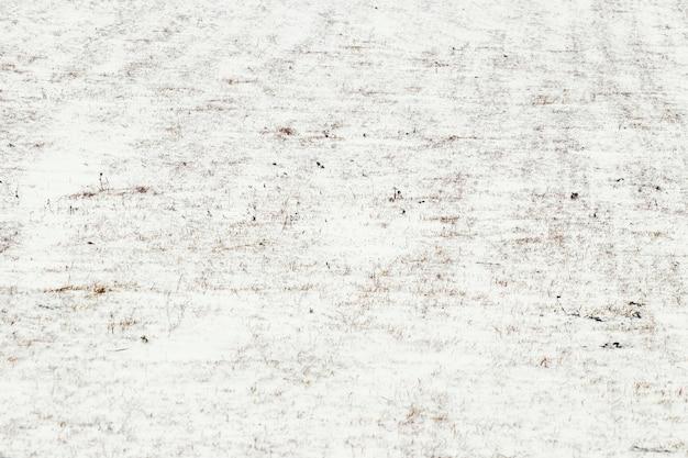 Champ couvert de neige avec de l'herbe sèche, fond d'hiver