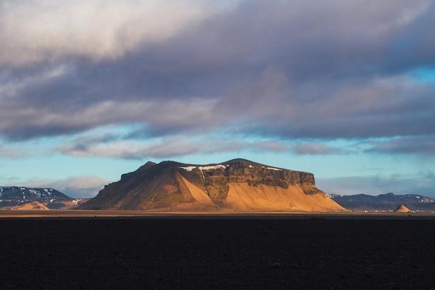 Champ entouré de rochers couverts de neige sous un ciel nuageux pendant le coucher du soleil en islande
