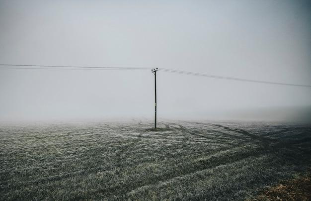 Champ givré avec poteau électrique dans un jour brumeux