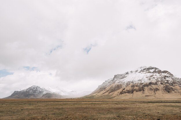 Un champ d'herbe jaune sèche de sommets enneigés en islande dans un ciel nuageux