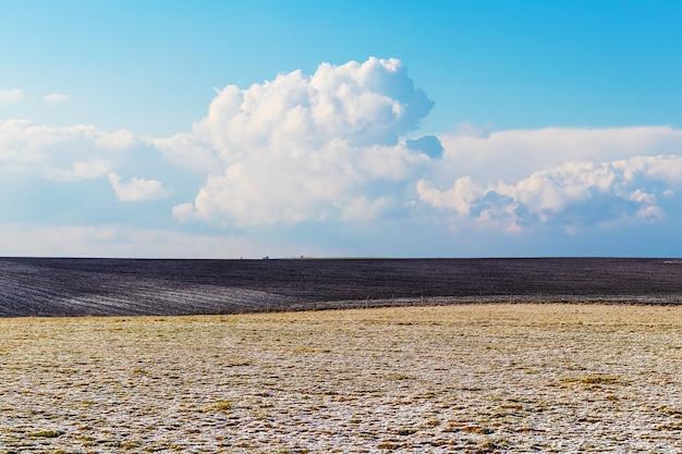 Le champ d'herbe sèche et de terre labourée est recouvert des premières neiges. nuages pittoresques sur le terrain