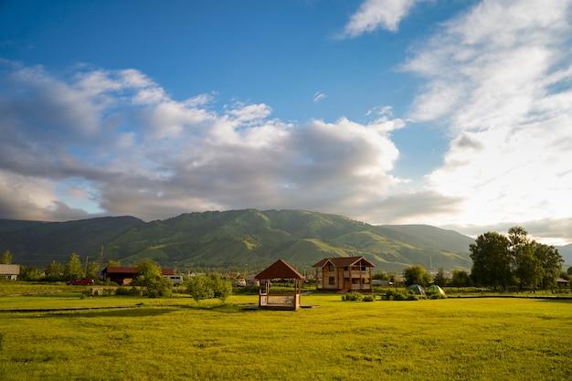 Champ d'herbe verte avec petit gazebo, chalet, tentes touristiques et montagnes