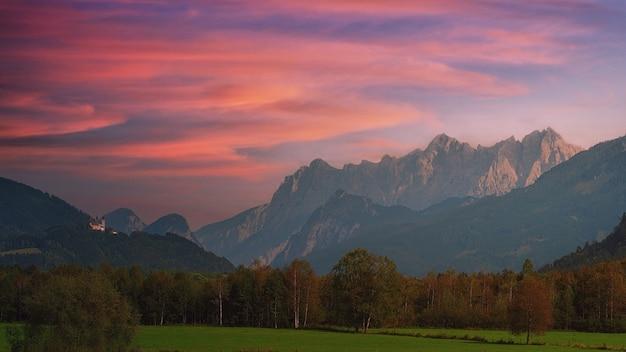 Champ d'herbe verte près de la montagne sous un ciel nuageux pendant la journée