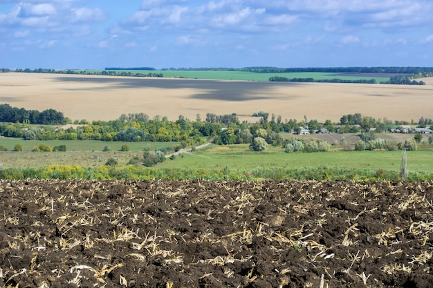 Un champ labouré après la récolte du maïs avec un tracteur équipé d'une charrue à huit corps