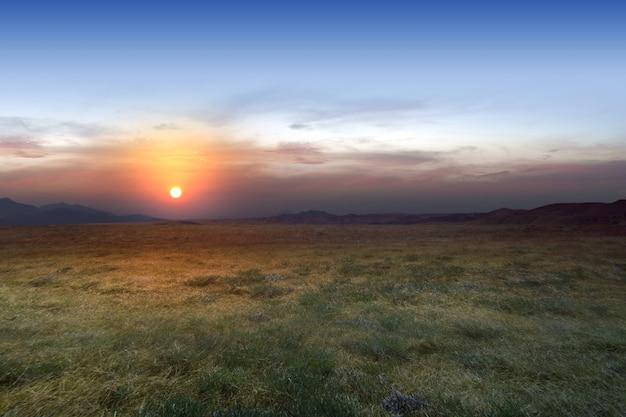 Champ de prairie avec un fond de ciel coucher de soleil