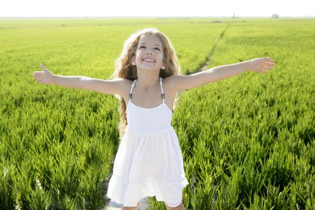 Champ de prairie verte bras ouverts petite fille heureuse