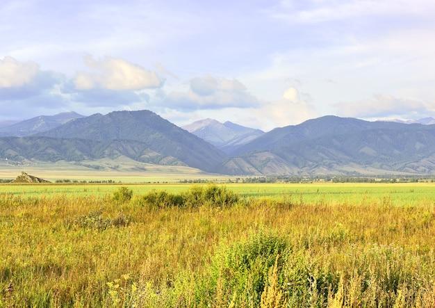Un champ rural parmi les montagnes de l'altaï sous un ciel bleu nuageux sibérie russie