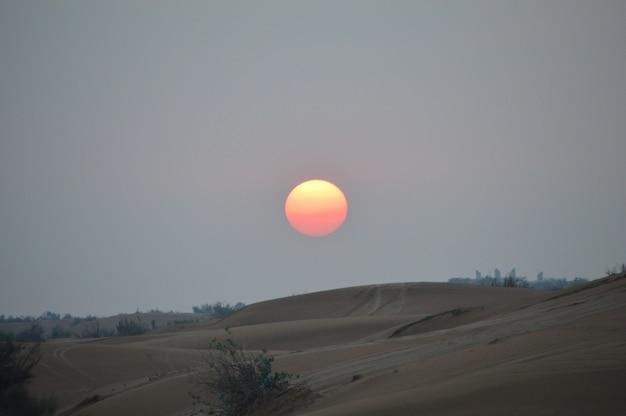 Champ de sable brun pendant le coucher du soleil