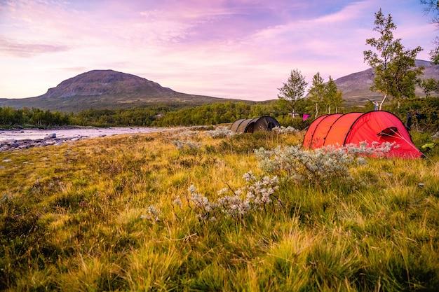 Champ avec des tentes entourées de collines couvertes de verdure sous un ciel nuageux pendant le coucher du soleil