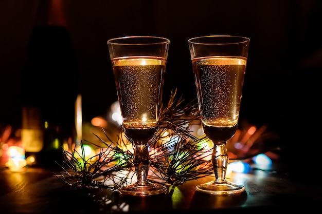 Champagne dans des verres, composition de noël ou du nouvel an avec des branches de sapin, des pommes de pin et une guirlande colorée brûlante, fond en bois vintage, mise au point sélective. la saint-valentin