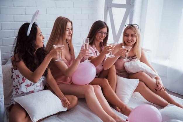 Le champagne est toujours important. assis sur le lit blanc de luxe avec des ballons et des oreilles de lapin. conception de bachelorette