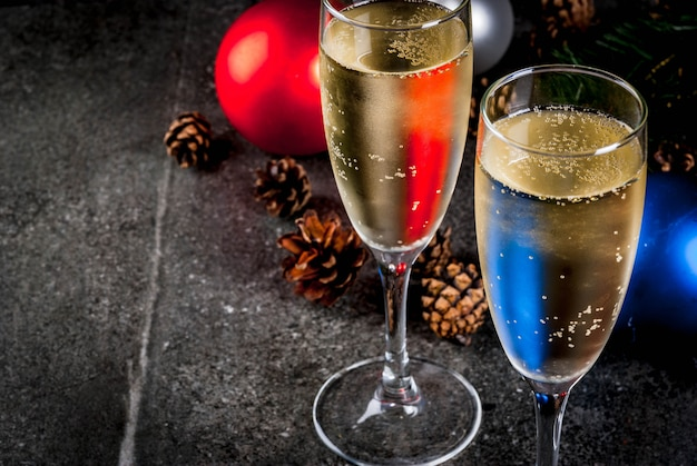 Champagne sec dans des verres, boules colorées de noël, pommes de pin, composition de nature morte du nouvel an sur fond de pierre sombre, mise au point sélective copy space