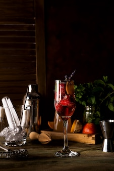 Champagne avec des tranches de brindilles de fraise et de lavande sur un fond en bois foncé