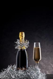 Champagne vue de face en bouteille et verre sur une surface sombre