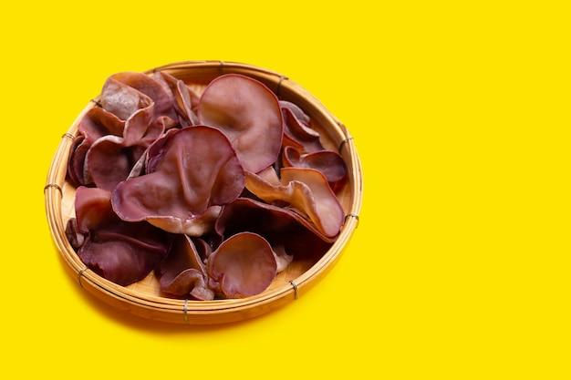 Champignon champignon noir dans le panier sur fond jaune.