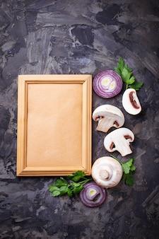 Champignon frais, oignon rouge et cadre pour texte. vue de dessus