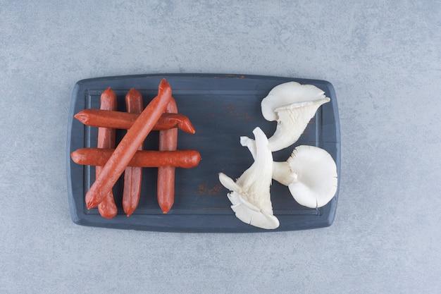 Champignon huître et salami sur tableau noir.