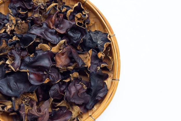 Champignon noir séché dans un panier en bambou sur fond blanc.