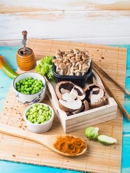 Champignon; pois verts; choux de bruxelles; pimenter; et moulin à épices sur napperon de cuisine