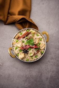 Champignon savoureux ou riz aux champignons ou pulav ou pilaf ou pulao ou biryani servi dans un bol ou une assiette, mise au point sélective