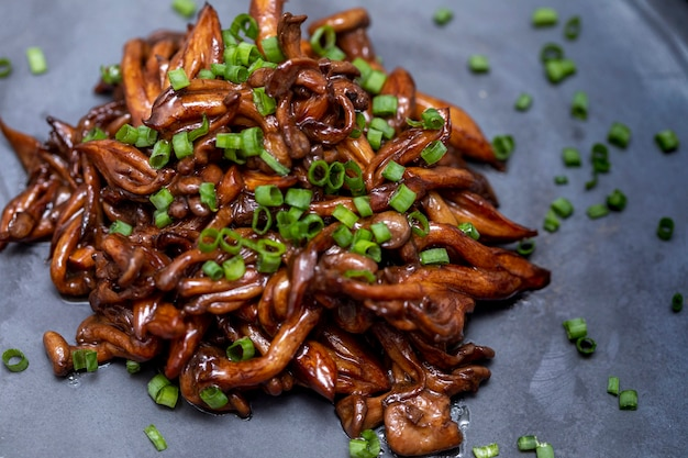 Champignon shimeji servi avec de la ciboulette sur plaque de pierre noire. repas oriental typique. détail du plat de nourriture, gros plan, mise au point sélective.