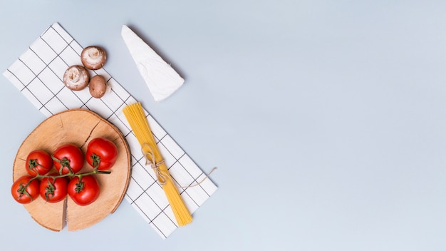 Champignon; tomates rouges; pâtes au fromage et spaghetti avec serviette de table sur fond gris