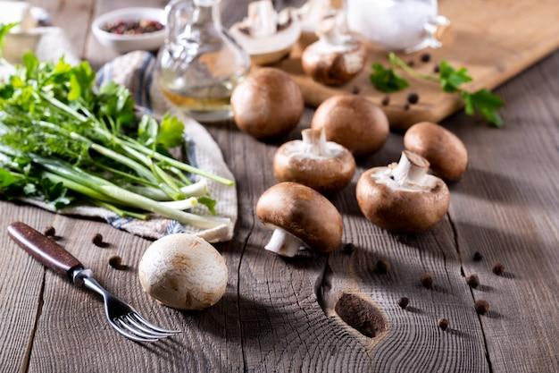 Champignons, aneth, persil, oignons verts sur une table en bois. produits pour la préparation de plats de champignons