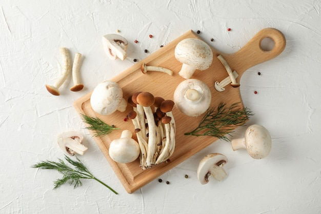 Champignons, aneth, planche et épices sur fond blanc, vue du dessus