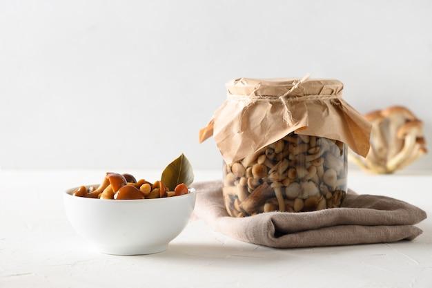 Champignons au miel marinés dans un bol et un pot sur fond blanc