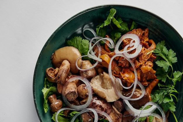 Champignons champignon dans un bol vert. champignons avec oignons et coriandre. oignons et champignons hachés. fond blanc. vue de dessus. espace de copie
