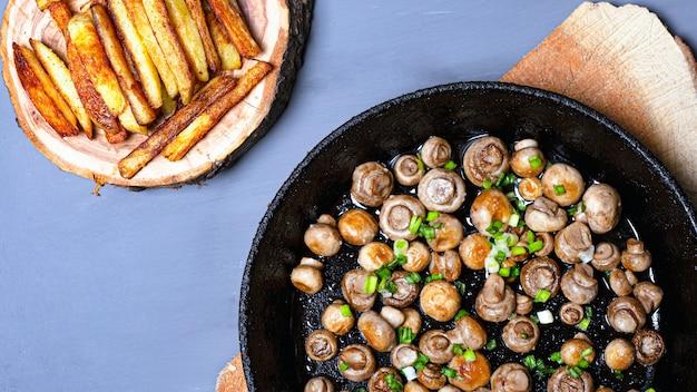 Champignons champignon frits dans une poêle en fonte avec des oignons verts et des frites sur un support en bois sur une vue de dessus de fond gris.