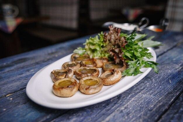 Champignons champignons cuits sur une table bleue râpée.